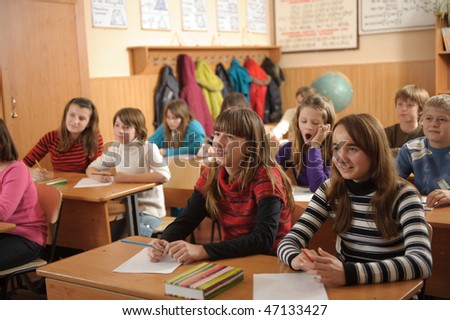 Group of schoolchildren during lesson. Cute girl at second desk is yawning. - stock photo