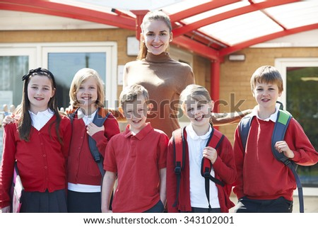 Group Of Schoolchildren With Teacher In Playground - stock photo