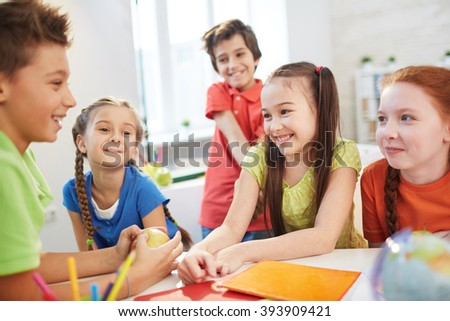 Group of schoolchildren working in team at the lesson - stock photo