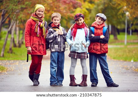 Group of schoolkids looking at camera outdoors