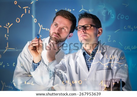 Group of scientists working at media screen in the laboratory - stock photo