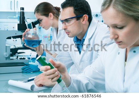 group of scientists working at the laboratory - stock photo