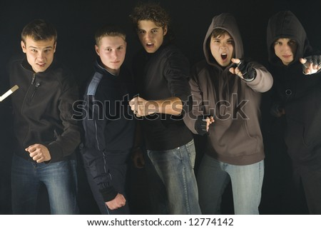 Group of screaming hooligans. They are looking at camera and standing in dark place. Two of them are pointing at camera. Front view - stock photo
