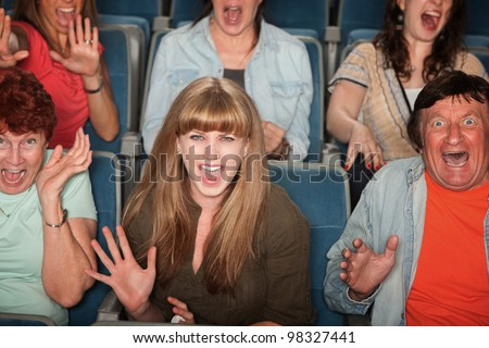 Group of screaming people at the movies - stock photo