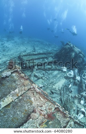 Group of scuba divers exploring the wrecked remains of a ship and its cargo. Yolanda reef, Ras Mohamed National Park, Red Sea, Egypt.