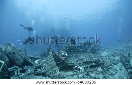 Group of scuba divers exploring the wrecked remains of a ship and its cargo. Yolanda reef, Ras Mohamed National Park, Red Sea, Egypt. - stock photo