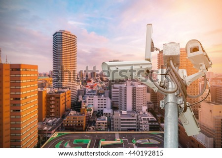 Group of security cameras (CCTV) on pole  with the sunrise in the morning at the big city background.