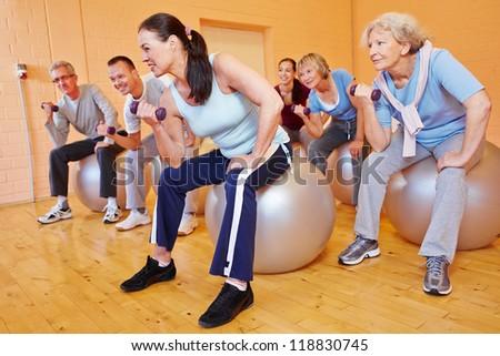 Group of senior citizens doing dumbbell training in gym - stock photo