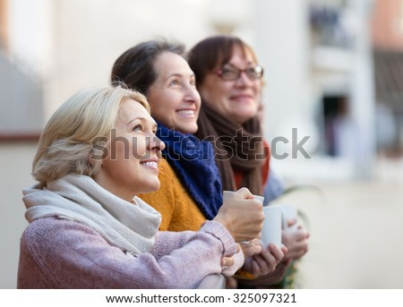 Group of senior female friends drinking tea at balcony and smiling. Focus on blonde - stock photo