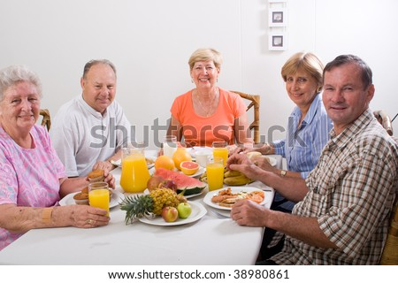 group of senior friends having breakfast together - stock photo