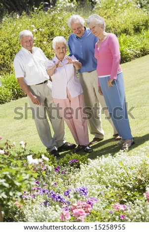 Group of senior friends in garden admiring flowerbed - stock photo