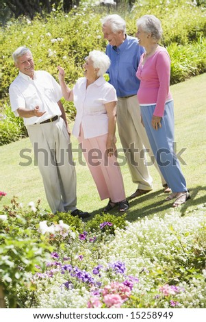 Group of senior friends in garden admiring flowerbeds - stock photo