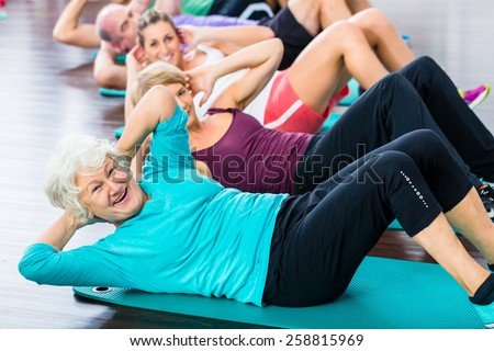 Group of senior people and young woman and men in fitness gym doing sit-ups on the floor - stock photo