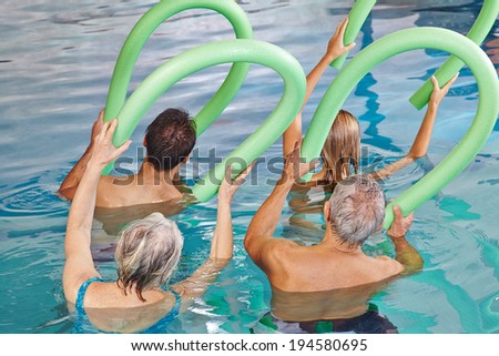 Group of senior people doing aqua fitness from behind with swim noodles - stock photo