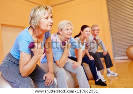 Group of senior people doing back training exercises in a gym - stock photo