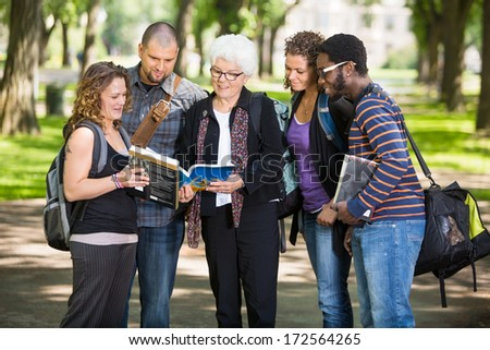 Group of senior students asking professor a question outdoors - stock photo