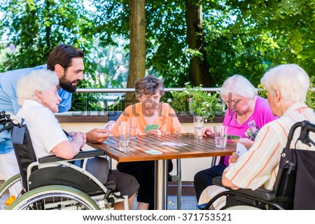 Group of seniors and nurse playing cards in rest home - stock photo
