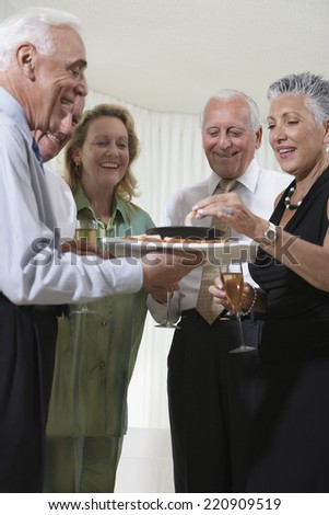 Group of seniors at party eating hors d'oeuvres - stock photo