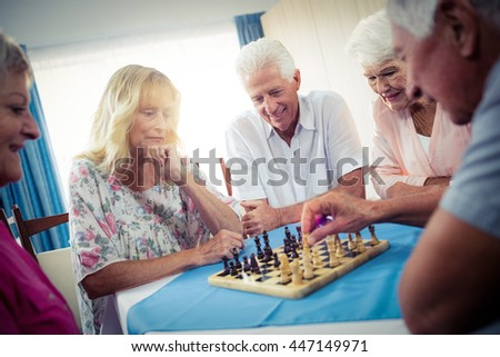 Group of seniors playing chess in the retirement house - stock photo