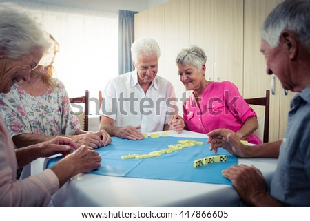 Group of seniors playing dominoes in the retirement house - stock photo