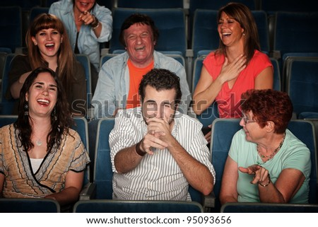 Group of seven audience watching movie laugh in theater - stock photo