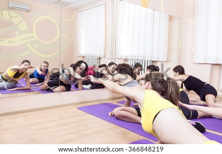 Group of Seven Caucasian Sportive Women Stretching Indoors on Sport Mats. Horizontal Image - stock photo