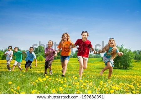 Group of seven happy running in the park kids, boys and girls, black and Caucasian - stock photo
