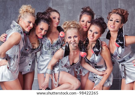 Group of seven happy smiling cute girls in silver go-go costume ready to party
