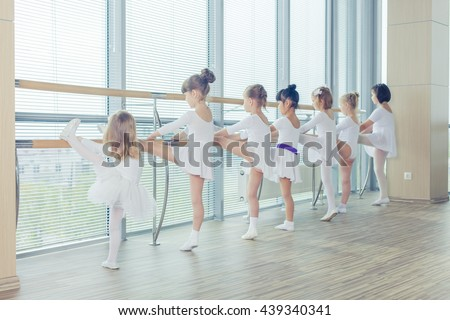 Group of seven little ballerinas standing in row and practicing ballet using stick on the wall - stock photo