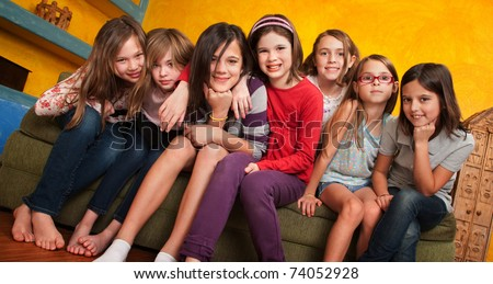 Group of seven little girls seated on a couch - stock photo
