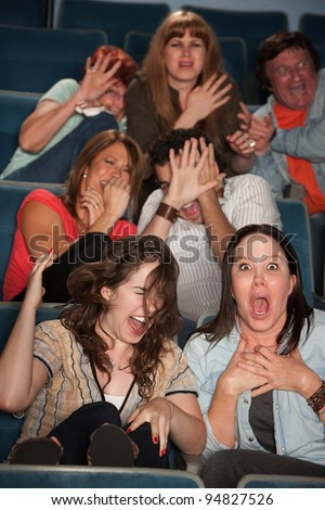 Group of seven scared audience members cringe in their seats - stock photo
