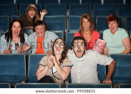 Group of seven scared people screaming in a theater - stock photo