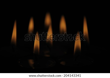 Group of several candle flames isolated over black background - stock photo