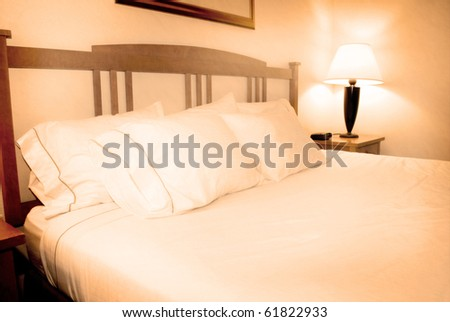 Group of several white pillows on a bed with headboard - stock photo