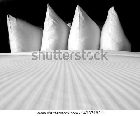 Group of several white pillows on a comfortable bed