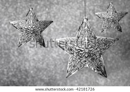Group of Silver Star With Snowflake Designs On Sparkling Gray Background - stock photo