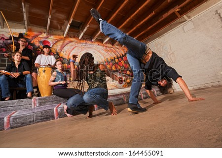 Group of six capoeira performers in urban building - stock photo