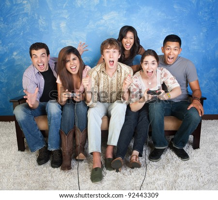 Group of six excited friends enjoy video games - stock photo