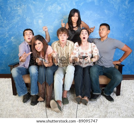 Group of six excited friends with controllers play video games - stock photo