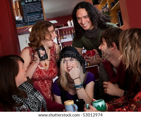 Group of six friends laughing over coffee - stock photo
