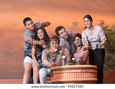 Group of six friends roast marshmallows over hot pot - stock photo
