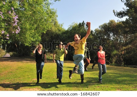 Group of six friends skipping through a park in the summer