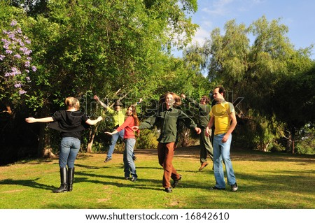 Group of six friends spinning around and jumping in a park - stock photo