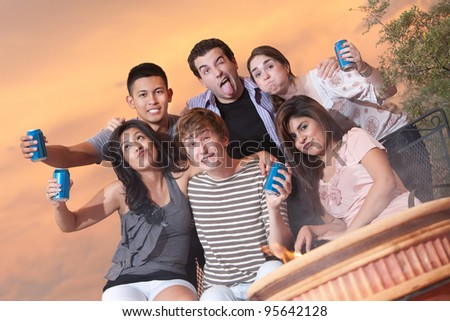 Group of six friends with beverage cans make funny faces