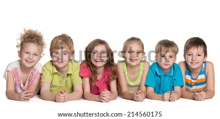 Group of six happy children are lying on the floor on a white background