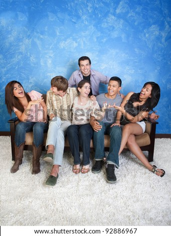 Group of six happy friends on sofa having fun - stock photo