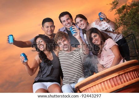 Group of six happy teens at an outdoor cookout - stock photo