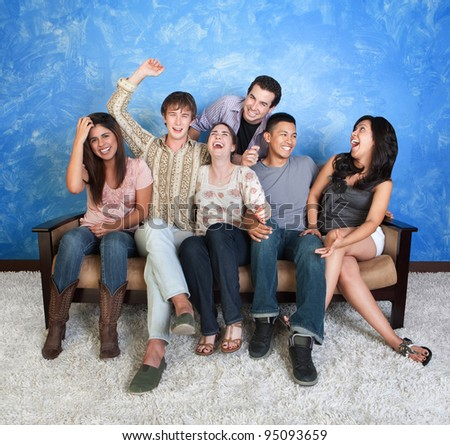Group of six happy teens on sofa laugh together - stock photo