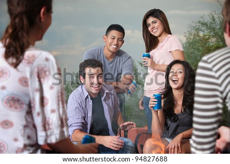 Group of six happy young people socialize outside