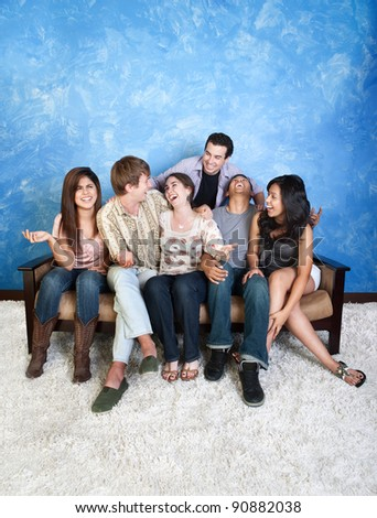 Group of six laughing friends on couch - stock photo
